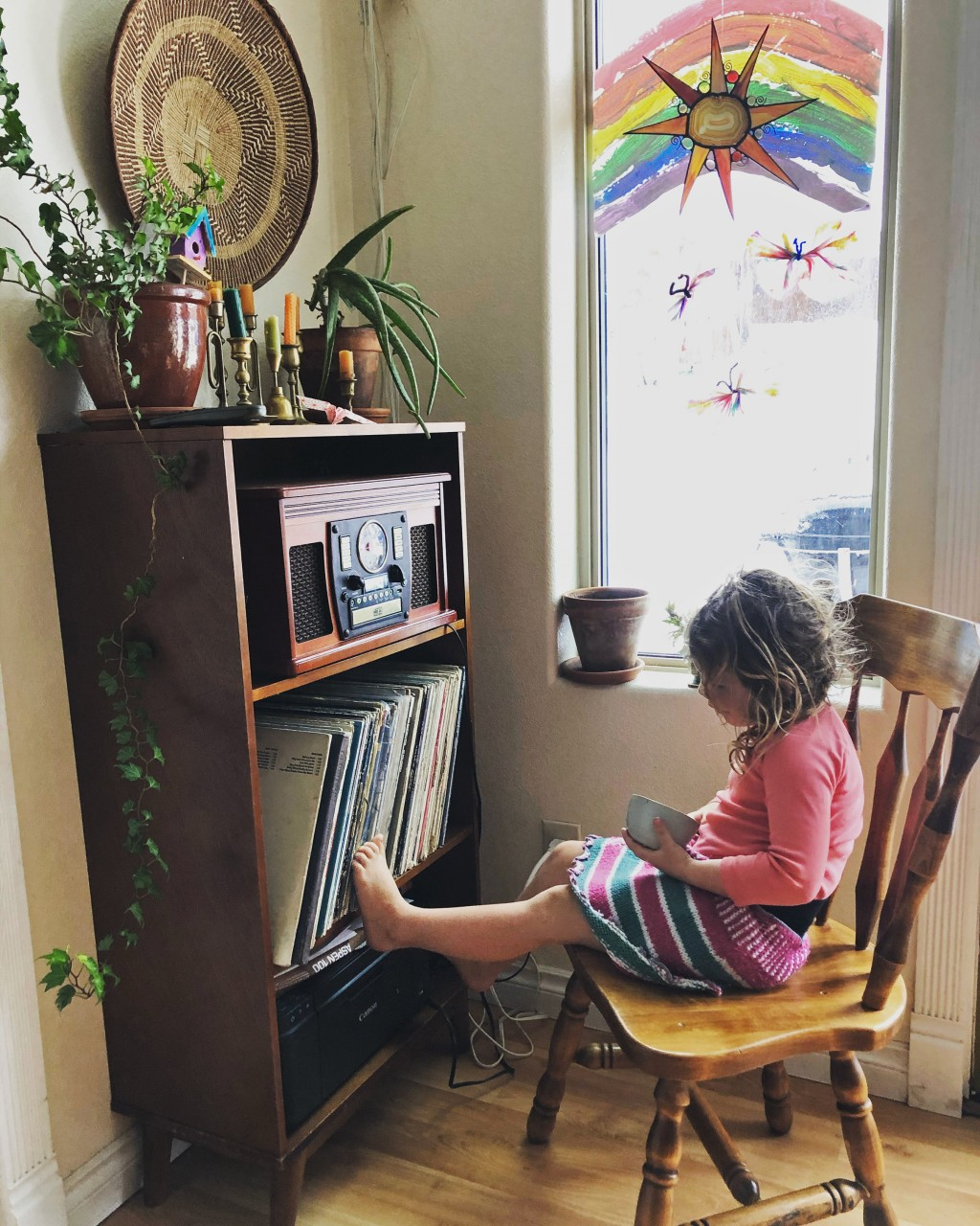 In this April 2, 2020, photo provided by Cassy Quinlan, 4-year-old Polly Fraley listens in Homer, Alaska, to children's stories being read on air at l...