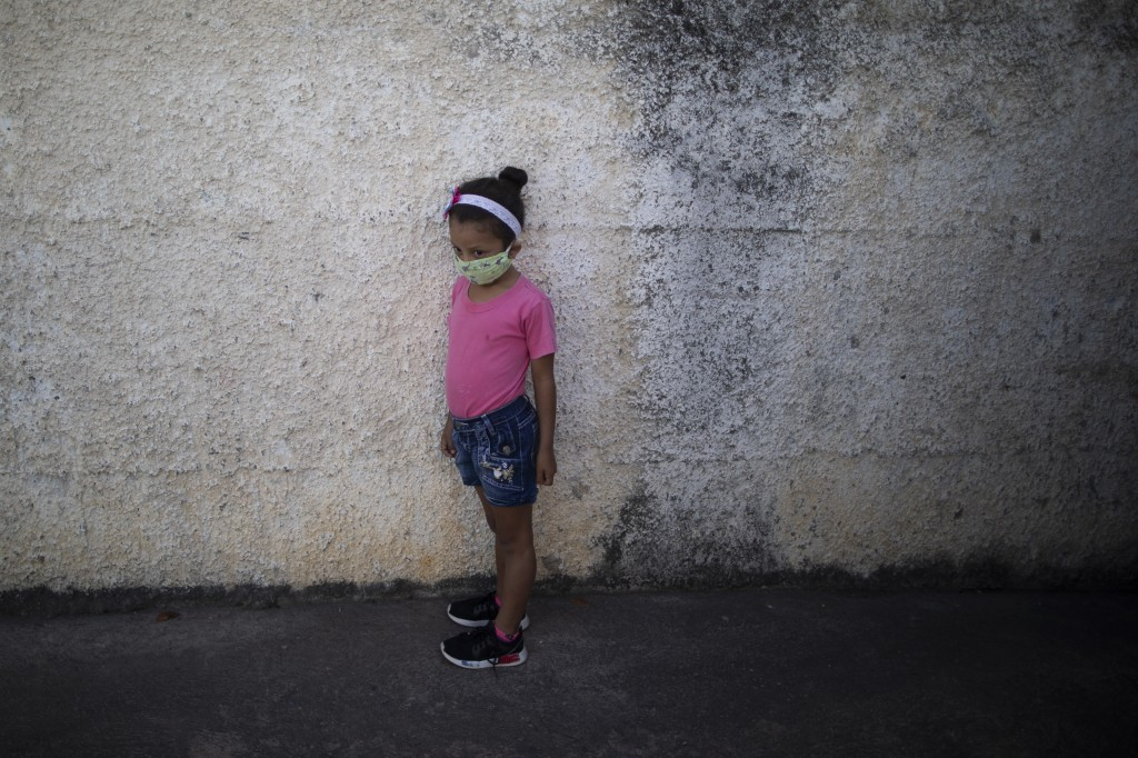 A girl wearing a mask to protect herself from the new coronavirus, waits at the entrance of the Fe y Alegria school as her mother drops off her homewo...