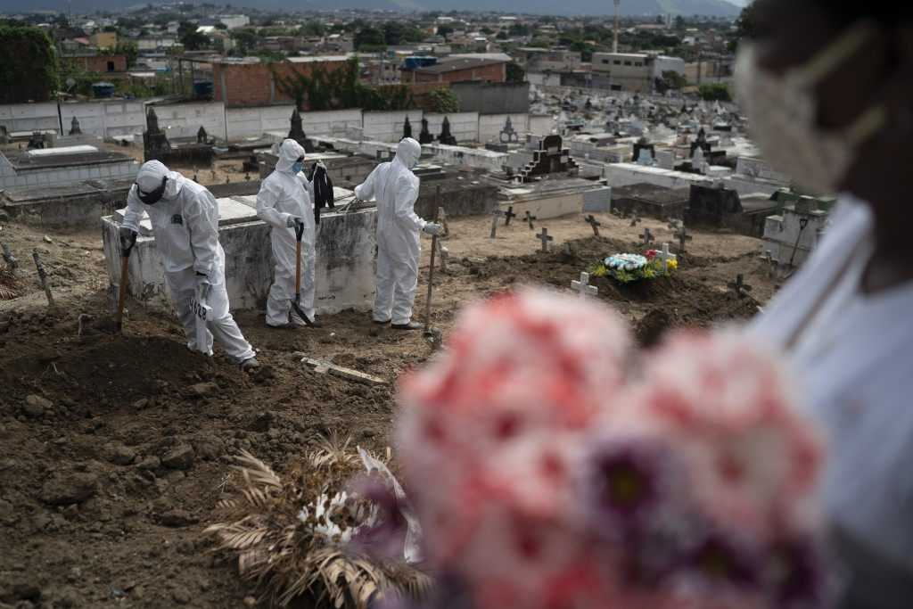 Cemetery workers wearing hazmat suits complete the burial of Ana Maria, a 56-year-old nursing assistant who died from the new coronavirus, in Rio de J...