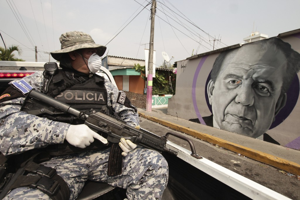 A National Civil Police Special Forces officer patrols past a mural of Armando Bukele, father of El Salvador's President Nayib Bukele, which was paint...