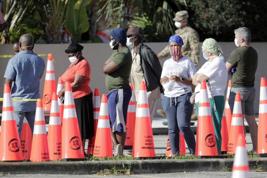 People wait in line to be tested for COVID-19 at a walk-up testing site outside of the Holy Family Catholic Church, during the new coronavirus pandemi...