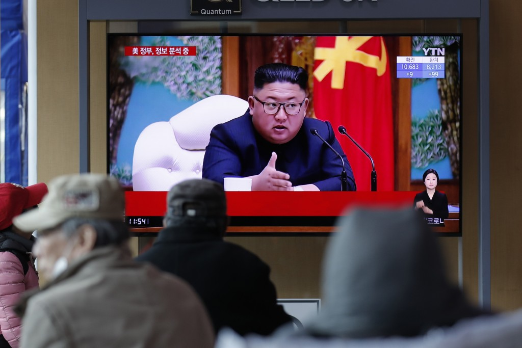 FILE - In this April 21, 2020, file photo, people watch a TV screen showing a news program reporting about North Korean leader Kim Jong Un with a file...