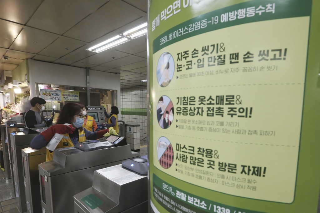 A worker disinfects ticket gates next to a poster about precautions against the new coronavirus at a subway station in Seoul, South Korea, Wednesday, ...