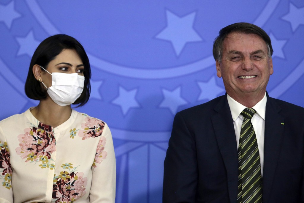 Brazil's President Jair Bolsonaro smiles sitting next to his wife Michelle Bolsonaro wearing a protective face mask, during the swearing ceremony of h...