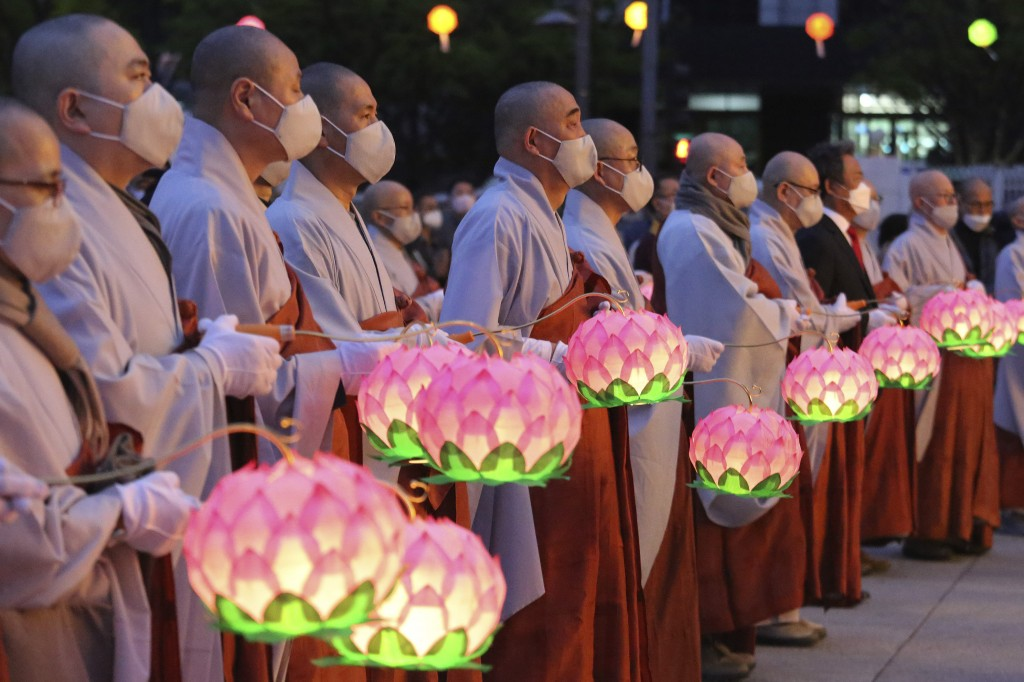 Buddhist monks wearing faces masks to help protect against the spread of the new coronavirus hold lanterns to celebrate the Buddha's birthday at the G...