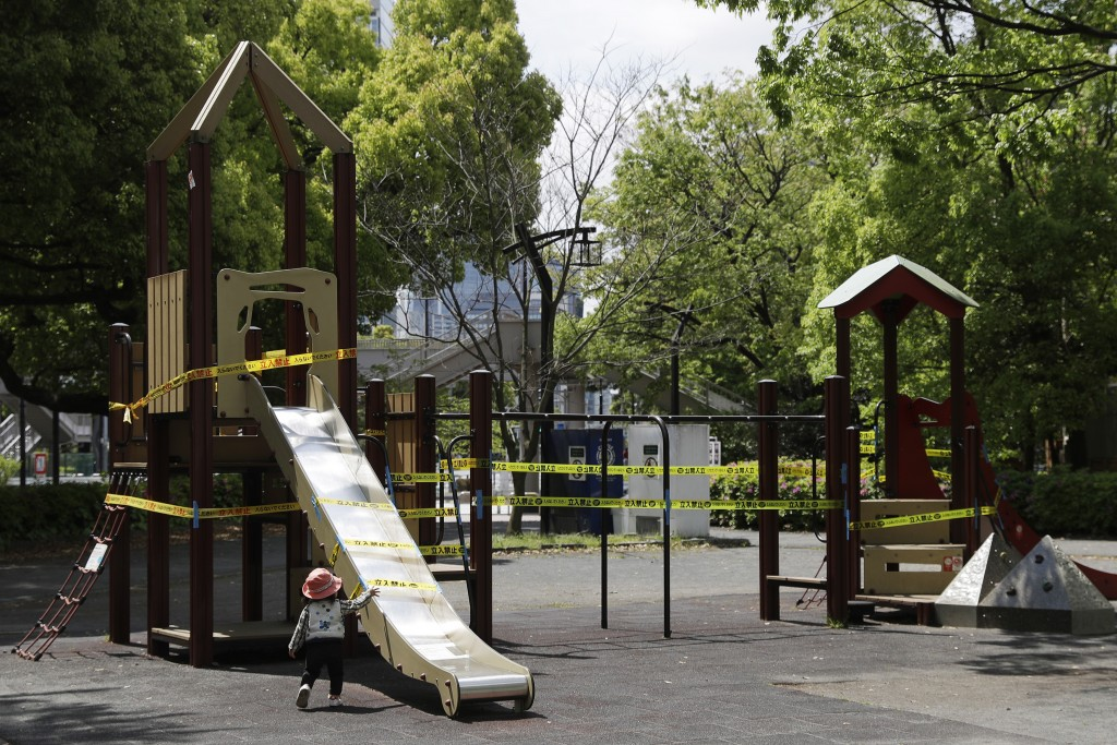 In this April 24, 2020, photo, a child walks past a slide cordoned off with ribbon reading, do not enter, in Tokyo. Under Japan's coronavirus state of...
