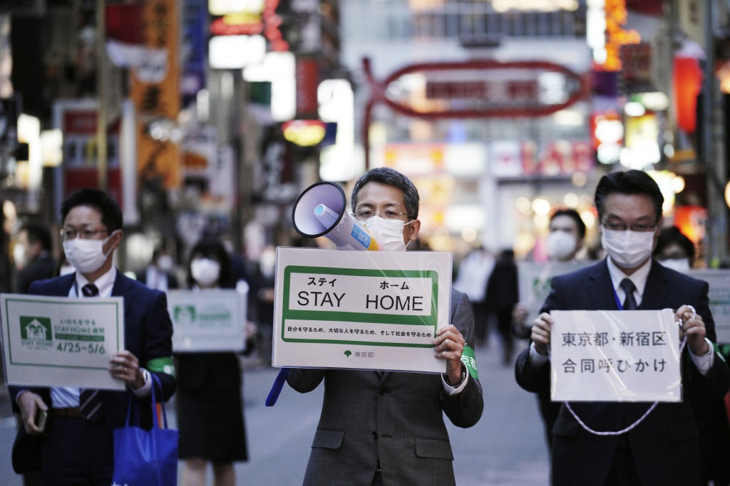FILE - In this April 24, 2020,  file photo, staff of the Tokyo Metropolitan Government urge people to go home from the Kabukicho entertainment distric...