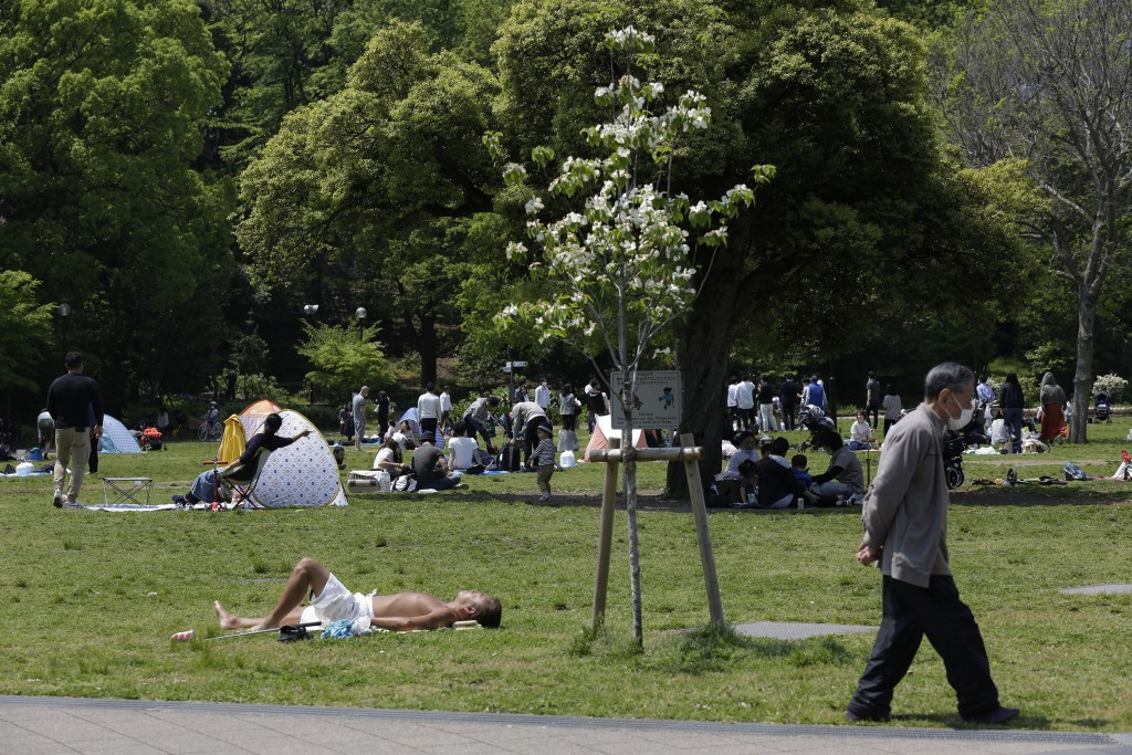 """In this April 29, 2020 photo, Shiba Park is packed with families with small children day camping in tents on the first day of the """"Golden Week"""" holida..."""