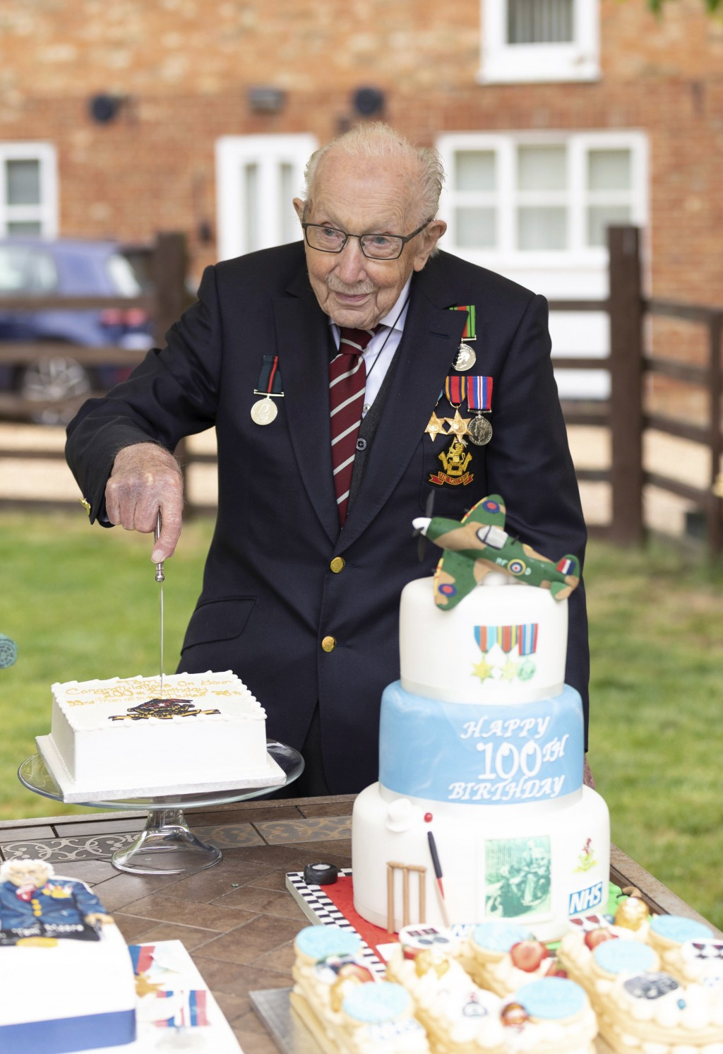 In this photo provided by Capture the Light Photography,  Second World War veteran Captain Tom Moore cuts into one of his birthday cakes as he celebra...