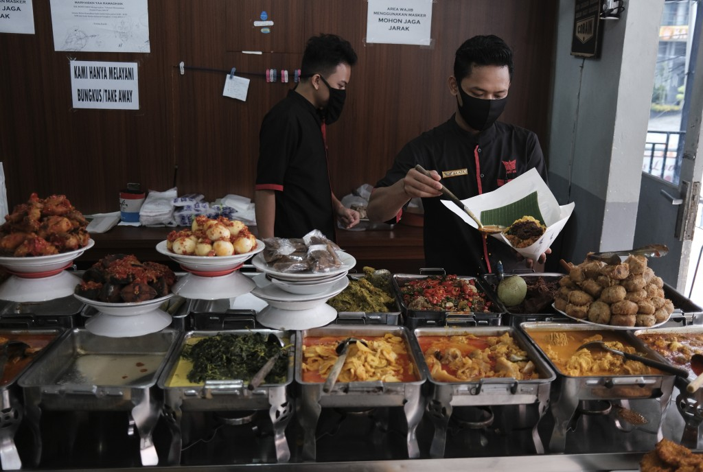 Restaurant workers wearing face masks as a precaution against the new coronavirus outbreak serve customers in Jakarta, Indonesia, Thursday, April 30, ...