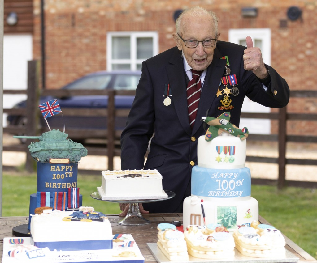 In this photo provided by Capture the Light Photography,  Second World War veteran Captain Tom Moore poses with birthday cakes as he celebrates his 10...