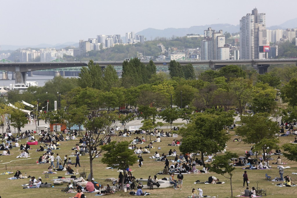 People enjoy at a public park on the Han River in Seoul, South Korea, Thursday, April 30, 2020. South Korean officials on Wednesday issued public plea...