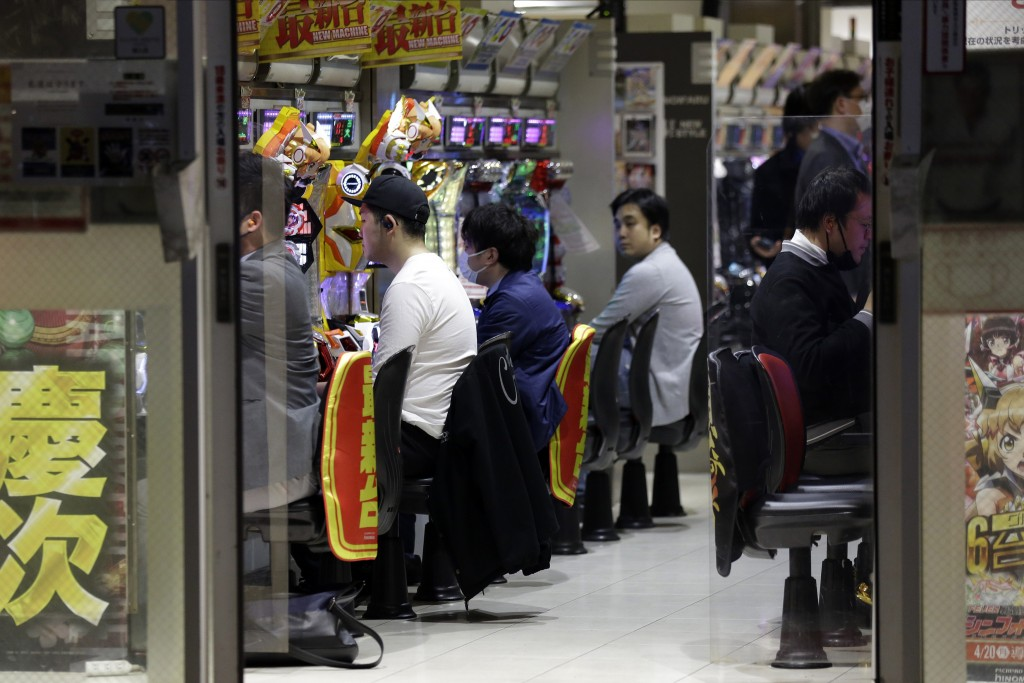 In this April 24, 2020, photo, patrons play at a pachinko gaming parlor in Tokyo. Under Japan's coronavirus state of emergency, people have been asked...