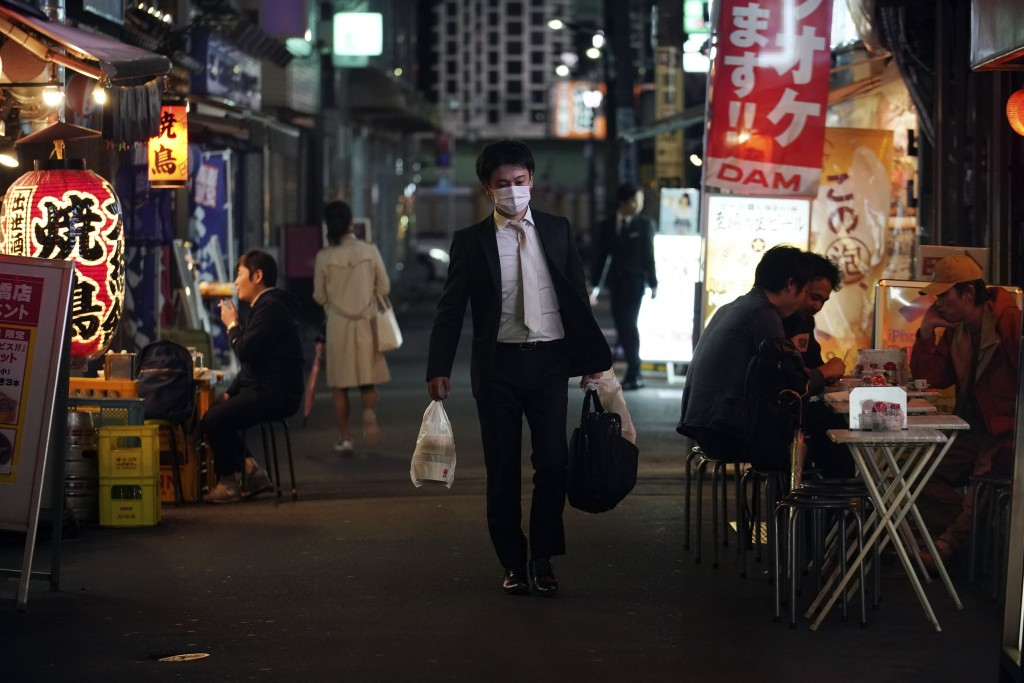 FILE - In this April 28, 2020, file photo, a man wearing a face mask against the spread of the new coronavirus walks through a bar street in Tokyo. Un...