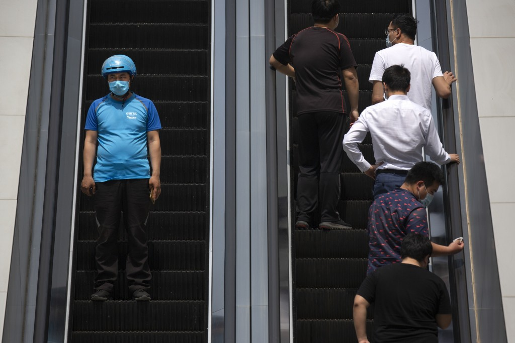 A deliveryman wearing a face mask to protect against the spread of the new coronavirus rides an escalator at an office plaza in Beijing, Thursday, Apr...