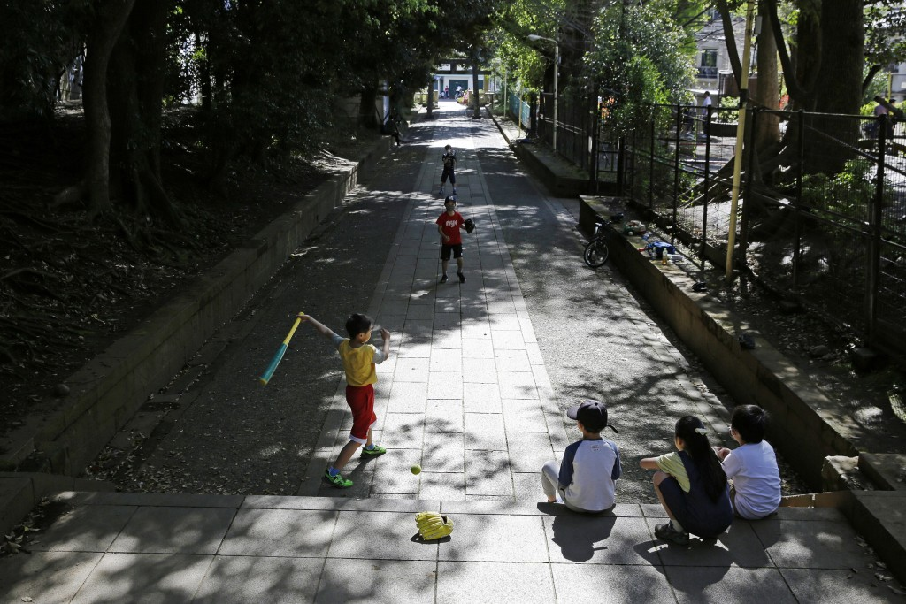 FILE - In this April 19, 2020, file photo, children, some wearing protective masks to prevent the spread of the coronavirus, play baseball on a walkwa...