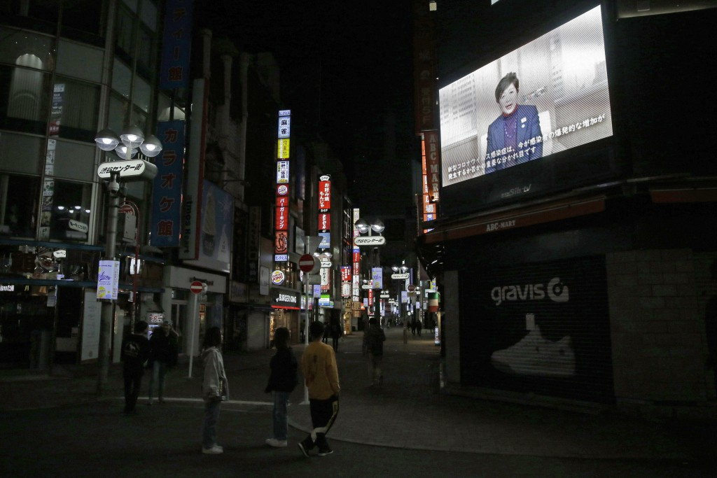In this April 25, 2020, photo, people walk through the entertainment district near Shibuya station right before the 8pm government requested closing t...