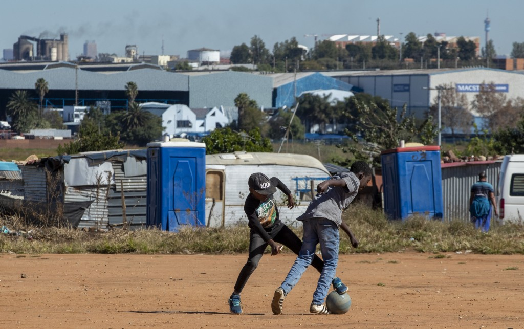 Young boys play soccer on a dusty field at Ramaphosa informal settlement, east of Johannesburg, South Africa, Tuesday, April 28, 2020. South Africa wi...