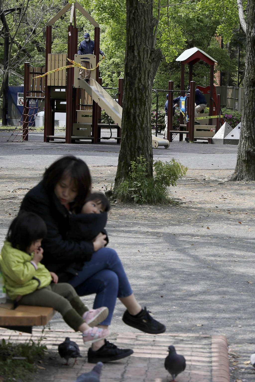 In this April 24, 2020, photo, a woman sits with her children as workers in background apply ribbon reading, do not enter, sealing off a playground in...