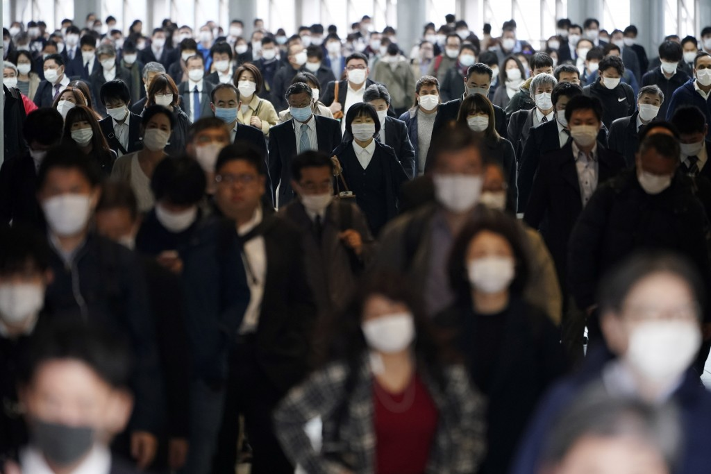 FILE - In this April 27, 2020, file photo, a station passageway is crowded with commuters wearing face mask in Tokyo. Under Japan's coronavirus state ...