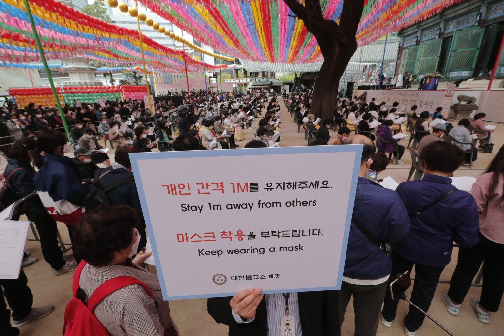 A Buddhist believer holds a notice about precautions against the new coronavirus during a service to pray for overcoming the COVID-19 outbreak and to ...