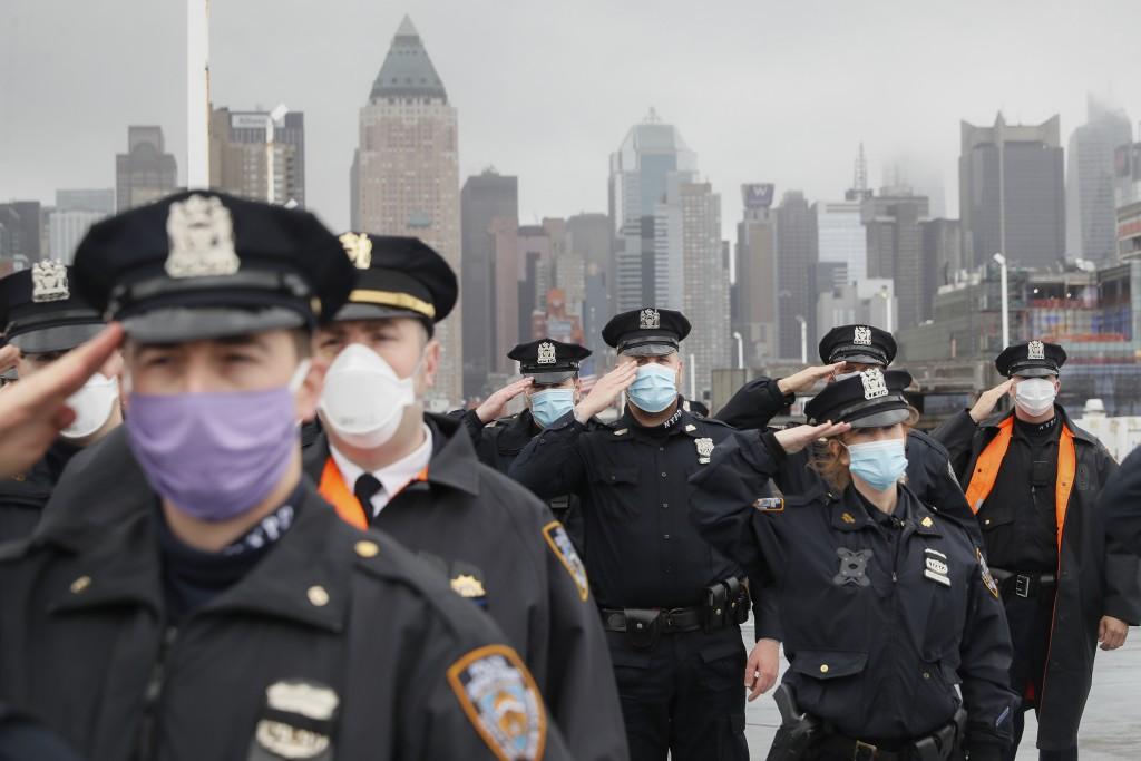 NYPD officers wearing masks to protect against cornavirus, salute the USNS Naval Hospital Ship Comfort as it is pushed out into the Hudson River by tu...