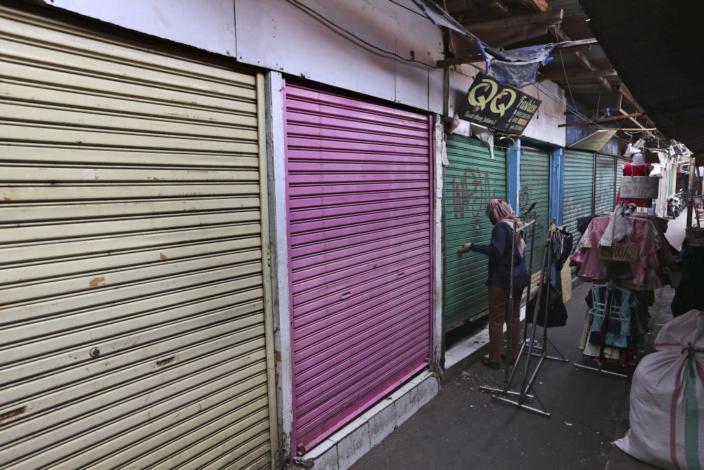 In this Thursday, April 30, 2020, photo, a woman closes her shop after collecting some leftover items at Tanah Abang textile market that is closed due...