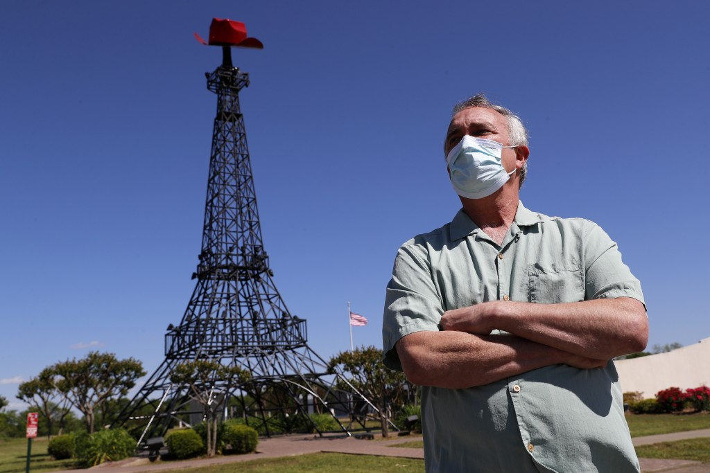 In this Wednesday, April 29, 2020, photo Mayor Steve Clifford poses for a photo in front of the town's iconic, small version of the Eiffel Tower, in P...