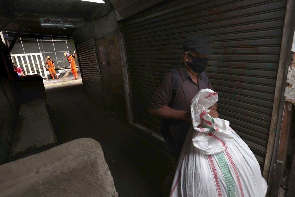 In this Thursday, April 30, 2020, photo, a man walks past closed shops as municipal workers sweep a sidewalk at Tanah Abang textile market that is shu...
