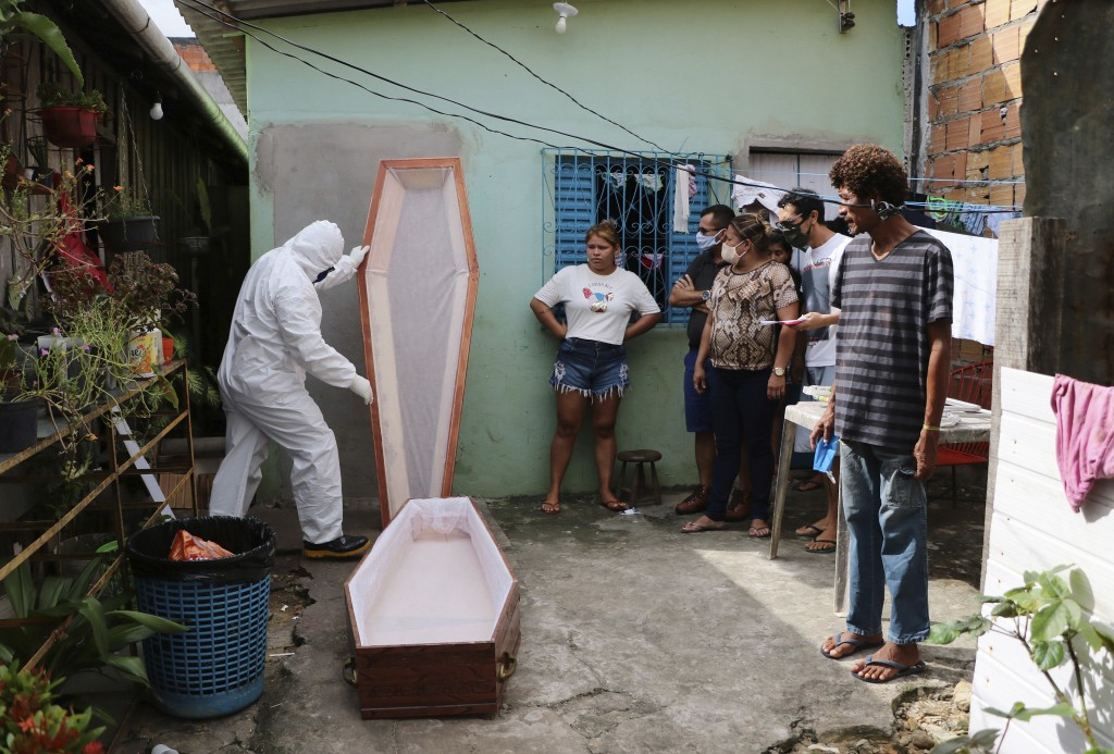 A funeral worker wearing protection gear prepares a coffin to remove thebody of Raimundo Costa do Nascimento, 86, who died at home amid the new corona...