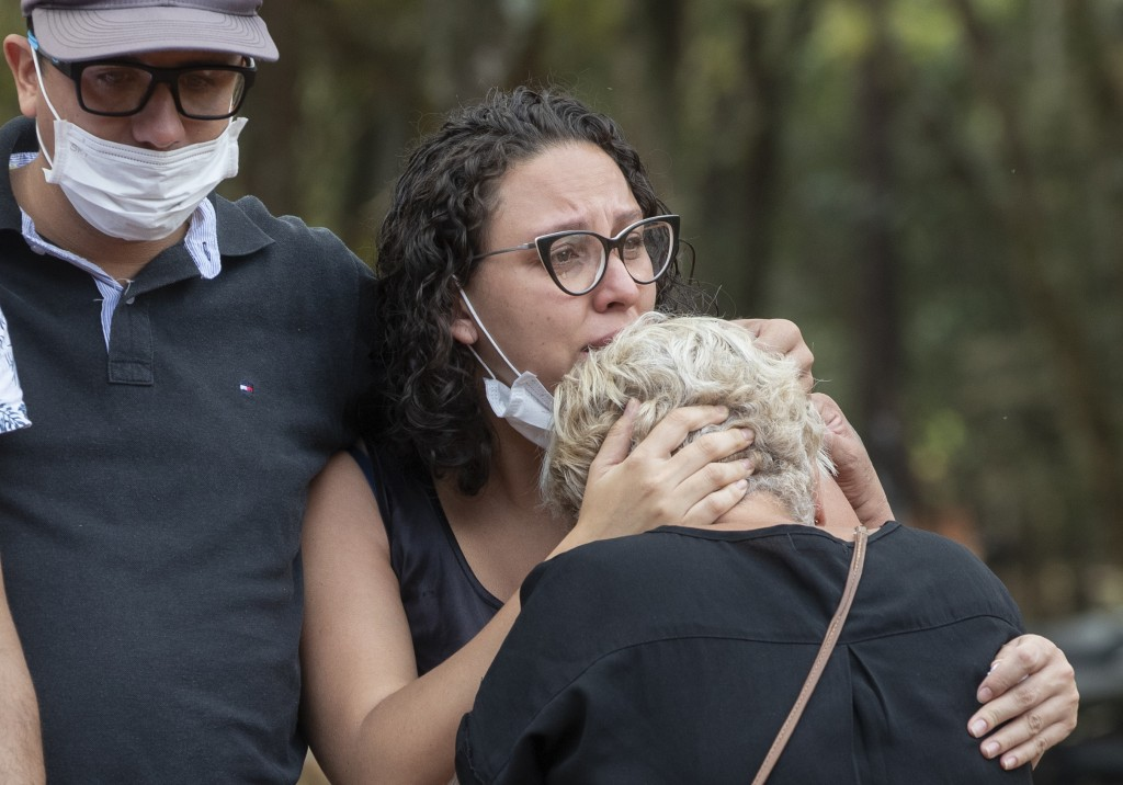 Relatives mourn at the burial of a person suspected to have died of COVID-19 disease, at the Vila Formosa cemetery in Sao Paulo, Brazil, Thursday, Apr...