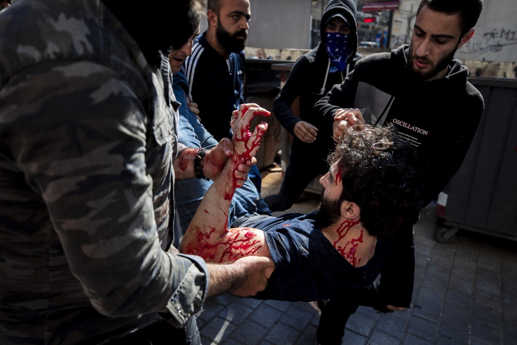 Anti-government protesters help a friend wounded during a scuffle with Lebanese army soldiers after the protesters tried to destroy bank windows durin...