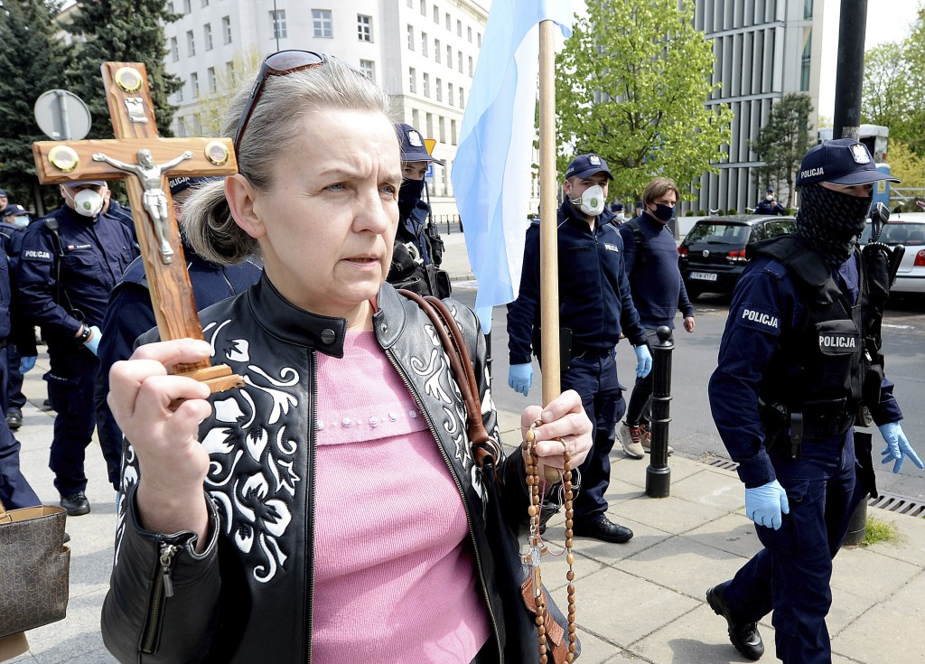 A woman holds a crucifix during an informal May Day gathering before the parliament building in Warsaw, Poland, on Friday, May 1, 2020. No official Ma...