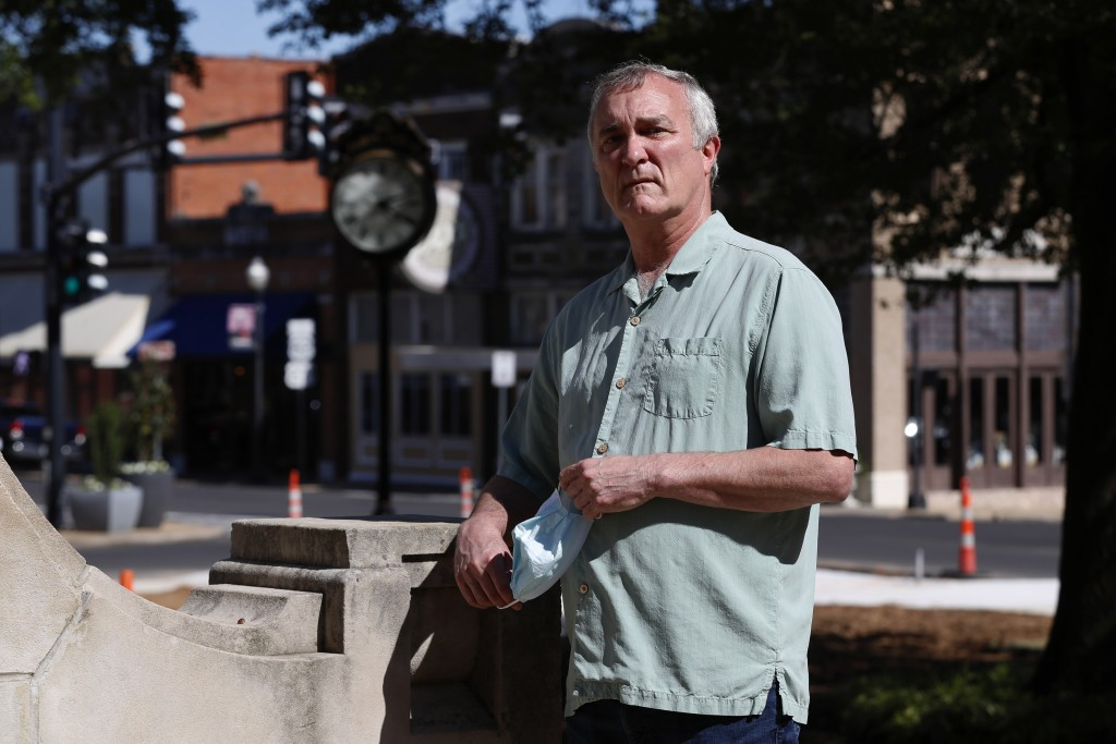 In this Wednesday, April 29, 2020, photo Mayor Steve Clifford removes his mask momentarily as he poses for a photo in the town square in Paris, Texas,...