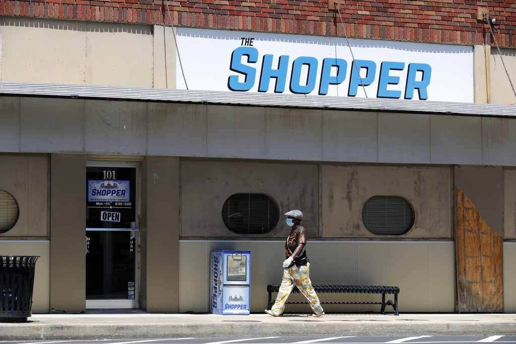 In this Wednesday, April 29, 2020, photo a person wearing gloves and a mask walks by The Shopper, a business off the town square in Paris, Texas. The ...