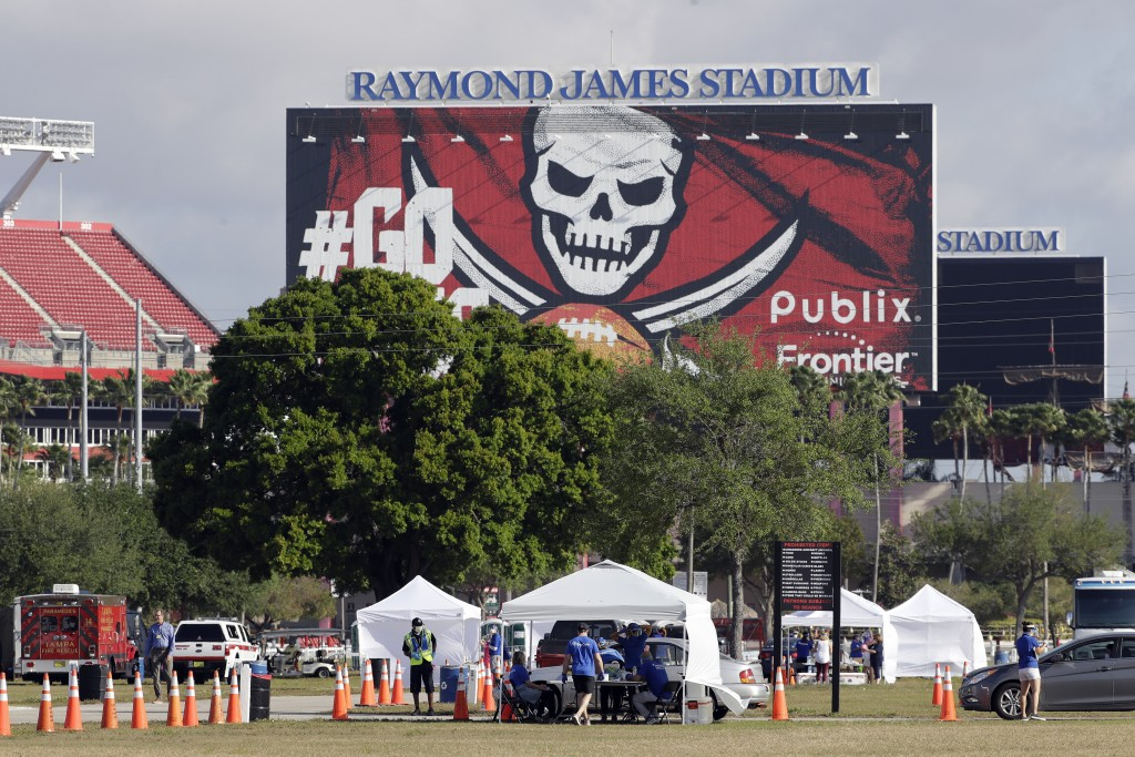 FILE - In this March 25, 2020, fikle photo, medical personnel from BayCare test people for the coronavirus in the parking lot outside Raymond James St...
