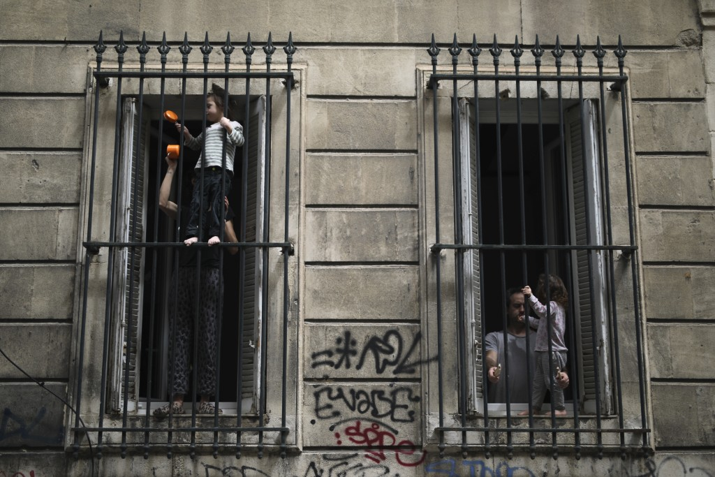 A confined couple and their children make some noise at their window Friday, May 1, 2020 in Marseille, southern France. France is bracing for potentia...