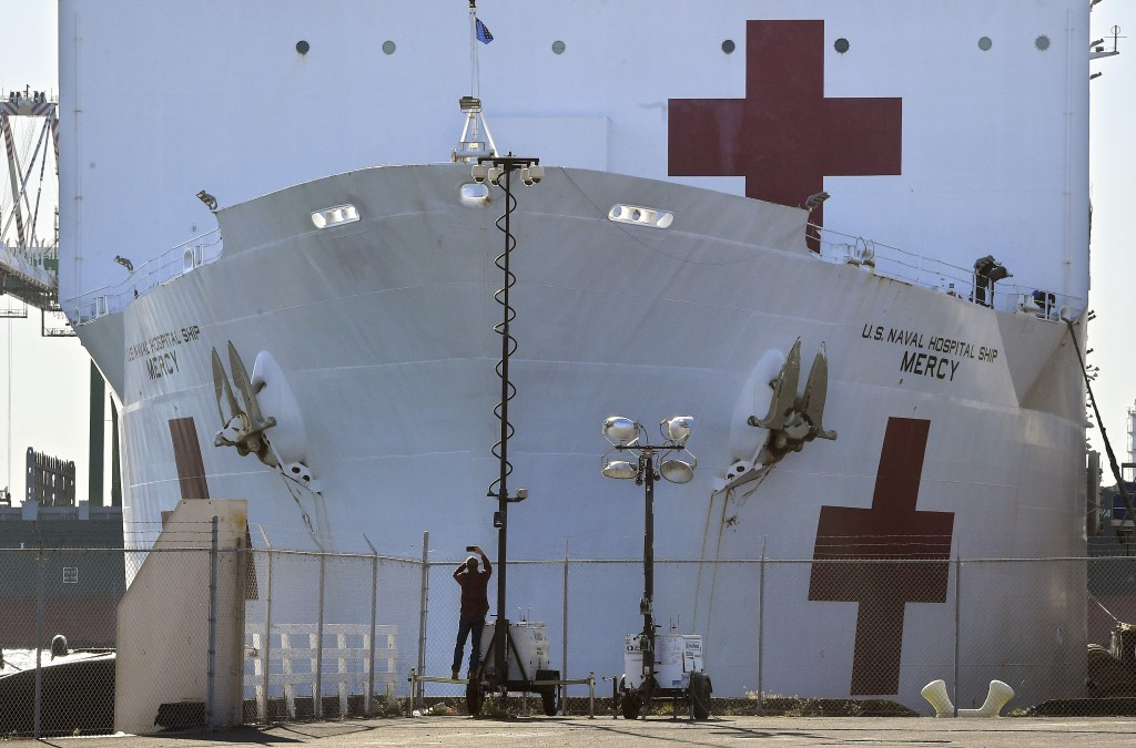 FILE - In this March 27, 2020, file photo, a pedestrian takes a picture of the USNS Mercy as it docks at the Port of Los Angeles. Los Angeles hasn't b...