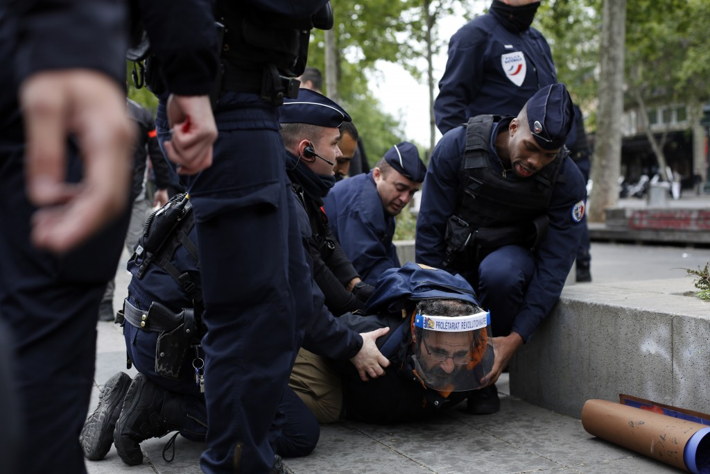 A man is arrested by police officers during a May Day demonstration, in Paris, during nationwide confinement measures to counter the Covid-19, Friday,...