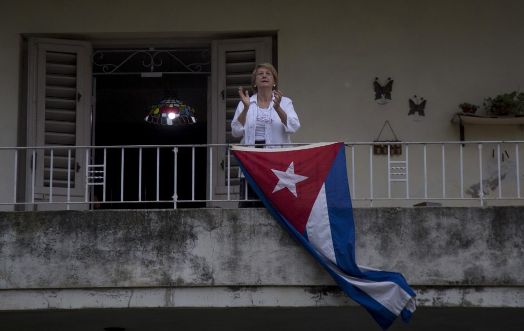 A woman claps from her home's balcony in celebration of May Day, or International Workers' Day, in Havana, Cuba, Friday, May 1, 2020. Due to the coron...