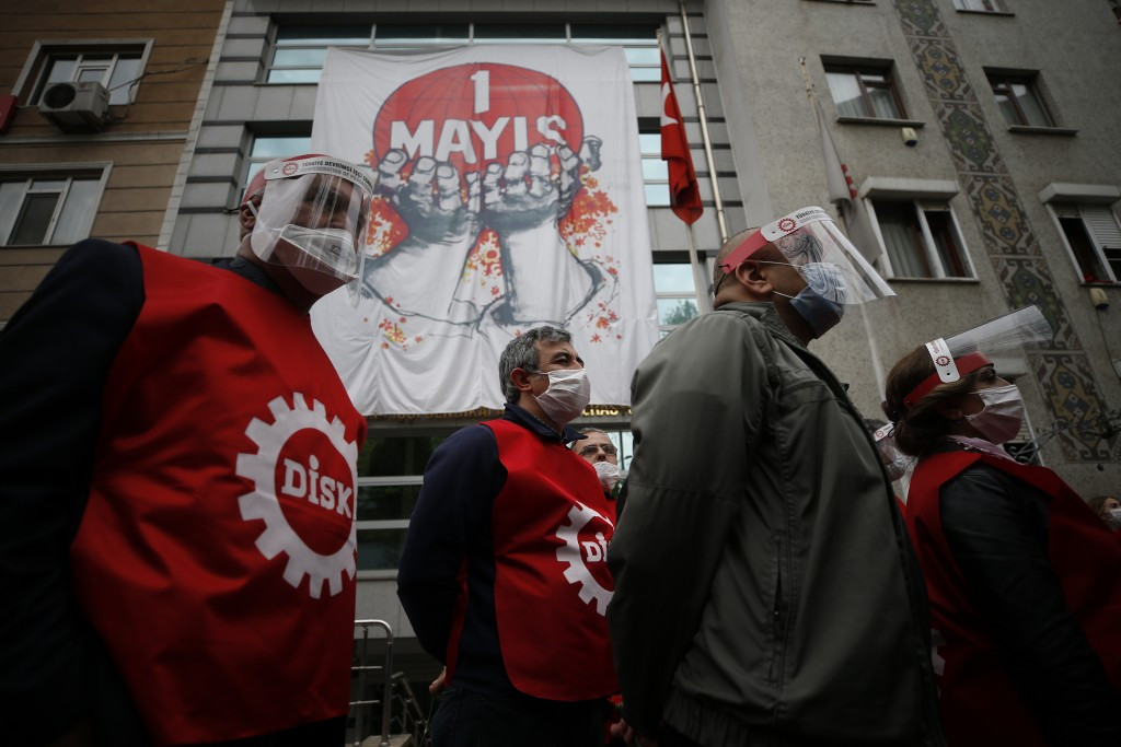 Demonstrators from the Confederation of Progressive Trade Unions of Turkey, or DISK, wearing face masks and shields for protection against the coronav...