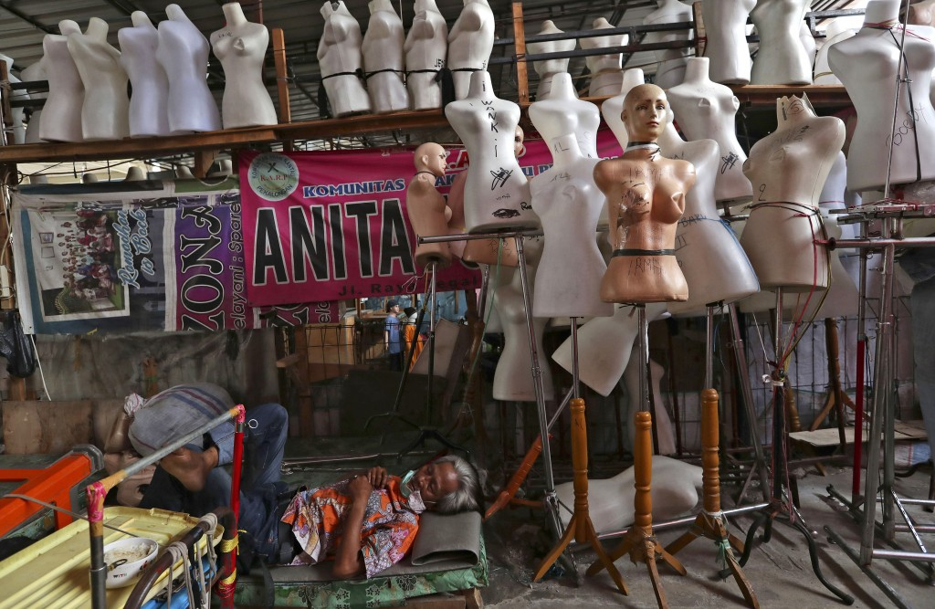In this Thursday, April 30, 2020, photo, a man naps among mannequins at Tanah Abang textile market that is closed due to the new coronavirus outbreak ...