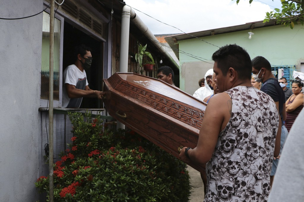 Relatives and funeral workers in protection gear move the coffin containing the remains of Raimundo Costa do Nascimento, 86, through a window of his t...