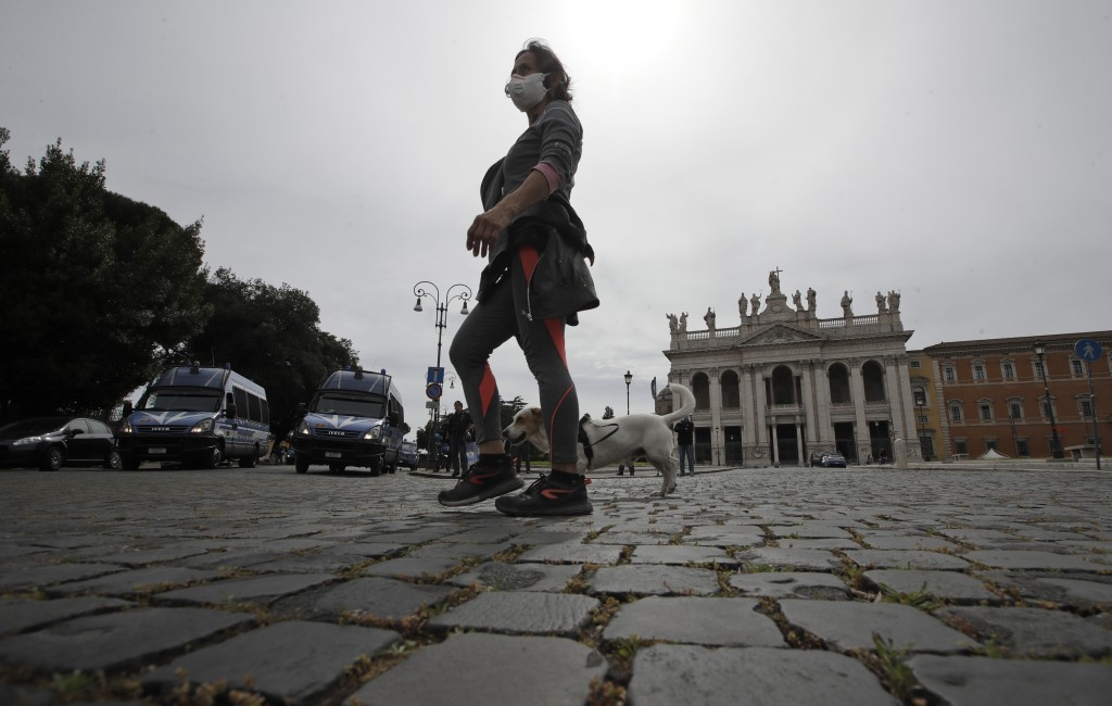 A woman wearing a mask to protect against COVID-19 walks in St. John at the Lateran Square, Friday, May 1, 2020. Italian Police patrol the square, whe...