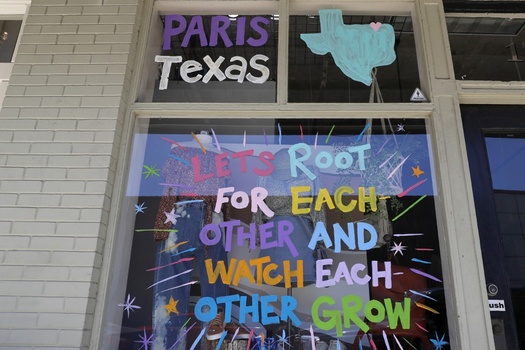 In this Wednesday, April 29, 2020, photo a painted message sits on the window of a business on the town square in Paris, Texas. The whiplash in Paris ...