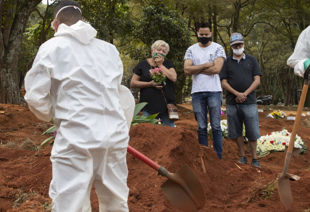 Relatives attend the burial of the remains of a person suspected to have died of COVID-19 disease, at the Vila Formosa cemetery in Sao Paulo, Brazil, ...