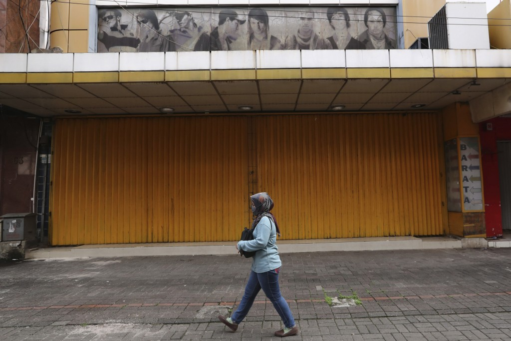 In this Thursday, April 30, 2020, photo, a woman walks past a shop closed due to the new coronavirus outbreak at Pasar Baru Shopping Center that is po...