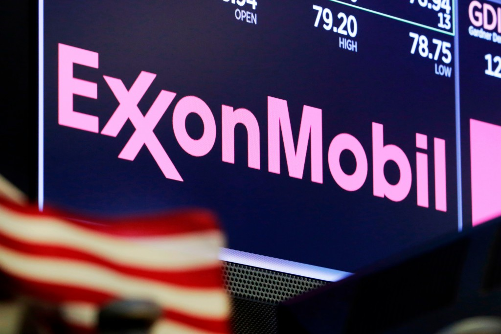 FILE - In this April 23, 2018, file photo, the logo for ExxonMobil appears above a trading post on the floor of the New York Stock Exchange.  Profits ...