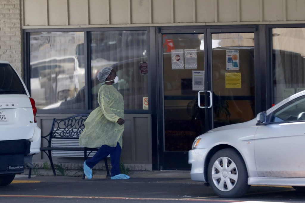 In this Wednesday, April 29, 2020, photo a worker in personal protective equipment was in to the Paris Healthcare Center in Paris, Texas. The whiplash...