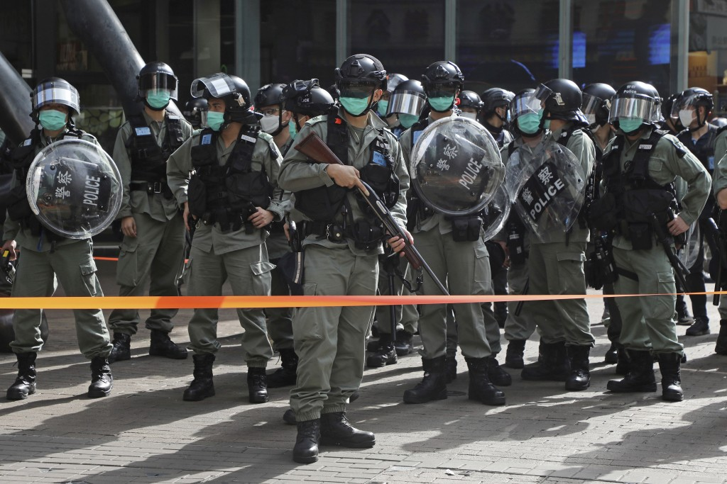 Riot police stand guard as pro-democracy activists gather outside a shopping mall during the Labor Day in Hong Kong, Friday, May 1, 2020 amid an outbr...